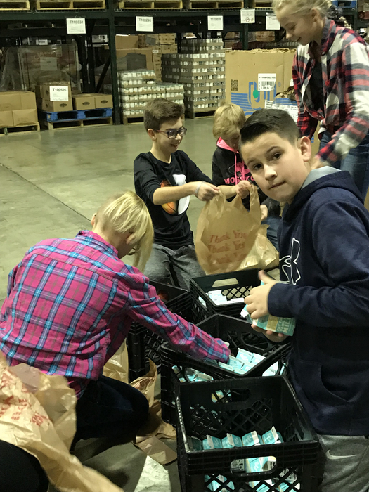 Warrior sixth graders volunteering at First Harvest Food Bank.